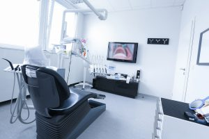 Dentists office with live picture of teeth in the background. Dental care dental hygiene checkup and therapy concept.