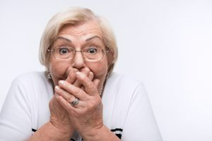 No evil. Pretty elderly woman covering her mouth with hands and gesturing three wise monkeys while standing over white background