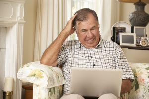 Frustrated Retired Senior Man Sitting On Sofa At Home Using Laptop